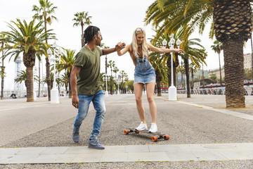 Spain, Barcelona, young man teaching his girlfriend skateboarding