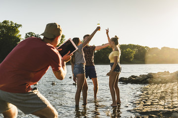 Group of happy friends with tablet in a river at sunset