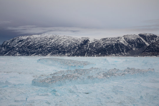 Tabular icebergs float in the Sermilik Fjord after a large calving event at the Helheim glacier near Tasiilaq, Greenland