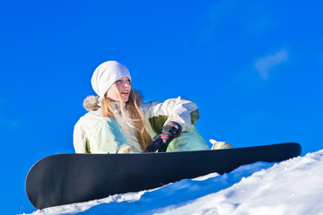 young woman with snowboard sitting on a slope of a hill