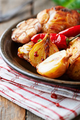 Oven-baked chicken with vegetables and fresh herbs. Homemade food. Symbolic image. Concept for a tasty and hearty dish. Rustic wooden background. Copy space.