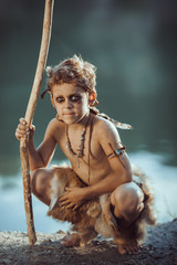 Cute caveman, manly boy with staff hunting. Prehistoric tribal boy outdoors on nature. Young shaggy and dirty savage, warrior and hunter. Primitive ice age man in animal skin sitting against river
