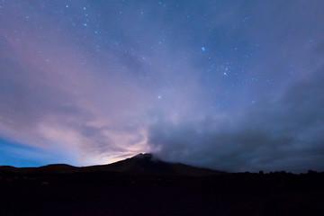 Vulkan unter Sternen und Wolken bei Nacht