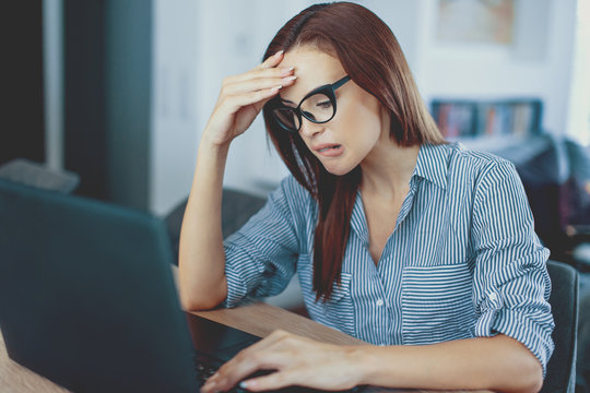 Frustrated young woman reading bad news on laptop screen