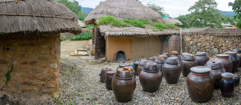 Vases of kimchi were lefted outside the house. Kimchi is a traditional and national food of Korean made with several vegetable mixed with chillies and preserved in the earthenware vesicle, pot or jar.