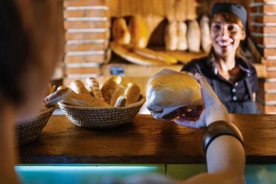 Saleswoman In Bakery Shop Serving Customers