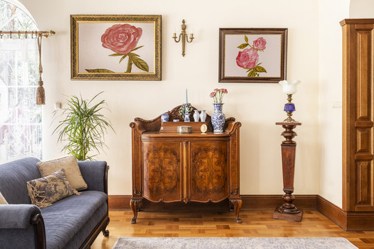 Real photo of an antique cabinet with porcelain decorations, paintings with roses and blue sofa in a living room interior