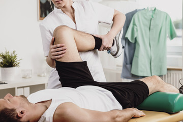 Physiotherapist helping patient with leg pain during treatment