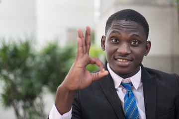 african businessman giving ok hand gesture; portrait of successful confident african business man showing success ok or okay gesture for winner, successful business deal; young adult african man model