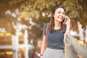 Junge, fröhliche Frau telefoniert mit dem Handy Wall mural
