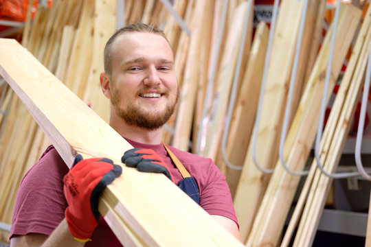 Smiling salesman or seller in construction store or warehouse wood section holding a pack of plankings