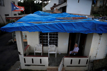 Lucila Cabrera, 86, sits at the porch of her house covered by plastic tarps over a damaged roof by Hurricane Maria, a year after the storm devastated Puerto Rico, near Barceloneta