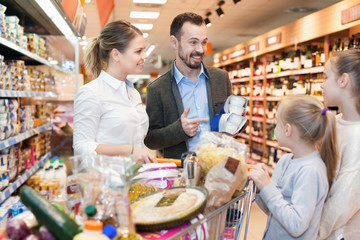 Family is looking on shelves with products in the supermarket.