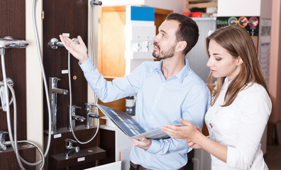 Family couple choosing for new modern functional shower mixer