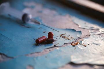 наркотики шприц таблетки и сигарета лежат на столе
