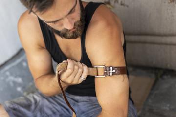 Intravenous junkie applying a belt as a tourniquet