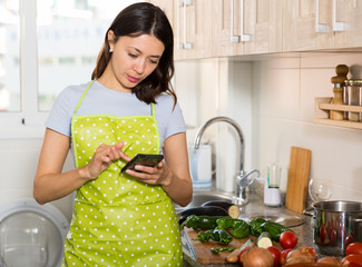 Young girl housewife in apron using phone at  kitchen