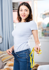 Slim glad young woman measuring waist with measuring tape