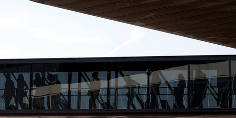 Pasengers walk on a jet bridge to board a plane at Nice International airport in Nice