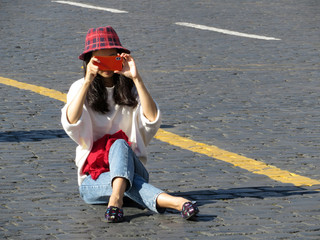 Girl sitting on the street with a smartphone and taking pics on mobile camera. Asian tourist, slim woman in jeans and hat outdoor