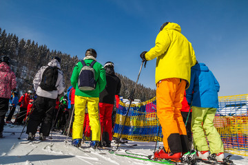 a few skiers in ski suits stand in line near the ski lift