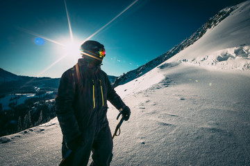 Masked Skier On The Side Of A Resort Mountain On A Sunny Day