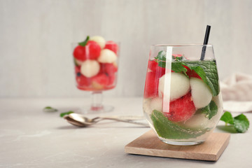 Glass with tasty melon and watermelon ball drink on gray table
