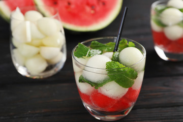 Glass with tasty melon and watermelon ball drink on dark table