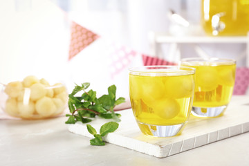 Glasses with tasty melon ball drink on light table