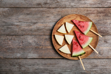Watermelon and melon slices on wooden background, flat lay. Space for text