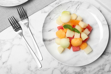 Salad with watermelon and melon on marble background, flat lay
