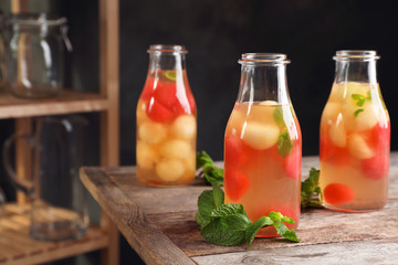 Bottles with tasty melon and watermelon ball drink on table