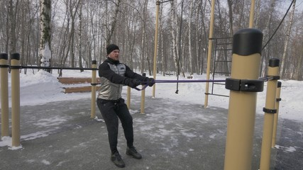 Bodybuilder training anaerobic exercise with expander on outdoor winter training