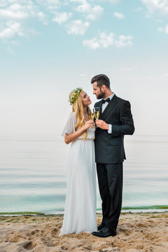 wedding couple clinking with glasses of champagne on beach and looking at each other