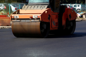 The large working machine of the skating rink makes a new asphalt. Road repair. Close-up