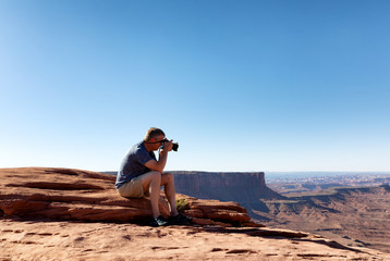 Mature man taking photos of the Grand Canyon while sitting down