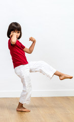 excited child showing her strength, enjoying exercising fun martial art