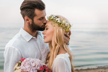 side view of handsome groom kissing attractive bride forehead on beach