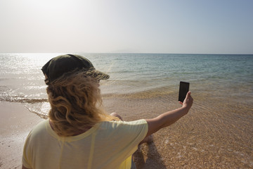 Young european woman taking selfie at morning sunny beach. Caucasian blond tourist with curly hair holding modern smart phone in hands and using digital camera. Travel and happy vacation concept.