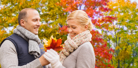 love, relationships and people concept - smiling couple with maple leaves over autumn park background