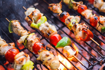 Fresh Vegetables And Marinated Meat On Bamboo Sticks On Barbecue Grill With Fire And Smoking Closeup