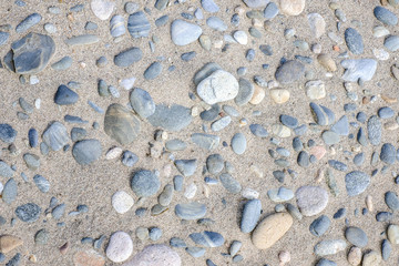 Background of sandy beach with different stones