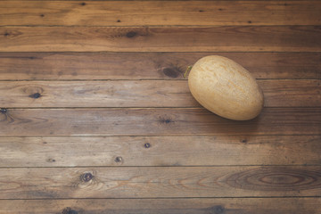 Huge yellow melon on a floor of a wooden terrace
