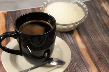 A cup of black coffee, a plate of pastry, and a bowl of sugar on a brown wooden background