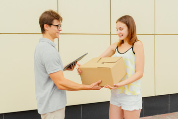 Young courier giving a parcel to cute girl