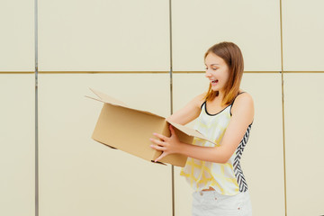 Cheerful young woman opening a cardboard box