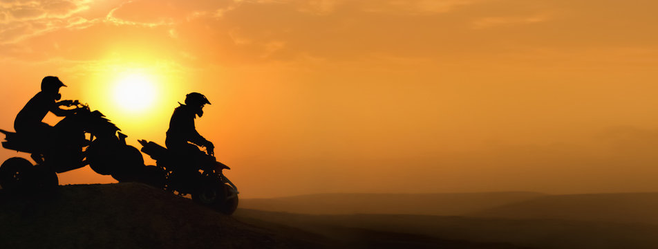 Silhouette ATV or Quad bikes Jump in sunset.