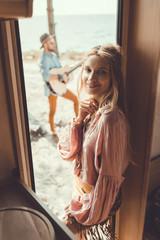 selective focus of smiling girl standing in door of campervan while man playing guitar behind