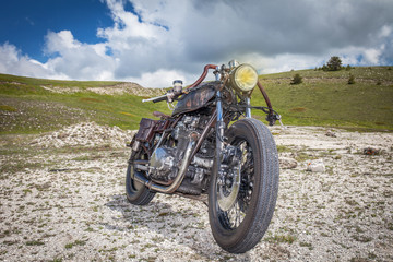 Rat custom motorcycle in a desolated mountain land. Post apocalyptic concept