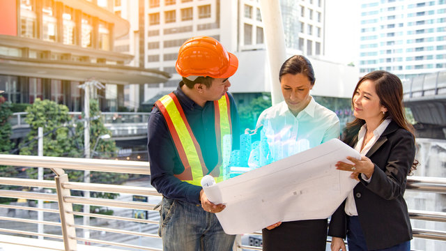 happy American women boss look at blueprint hologram plan.International joint venture to work construction building in city.